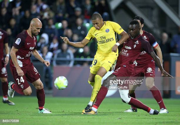Kylian Mbappe of PSG between Renaud Cohade and Moussa Niakhate of FC Metz during the French Ligue 1 match between FC Metz and Paris Saint Germain at...