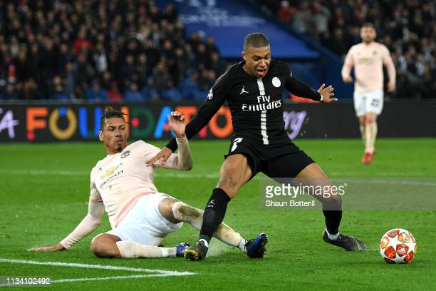 Kylian Mbappe of PSG is tackled by Chris Smalling of Manchester United during the UEFA Champions League Round of 16 Second Leg match between Paris...