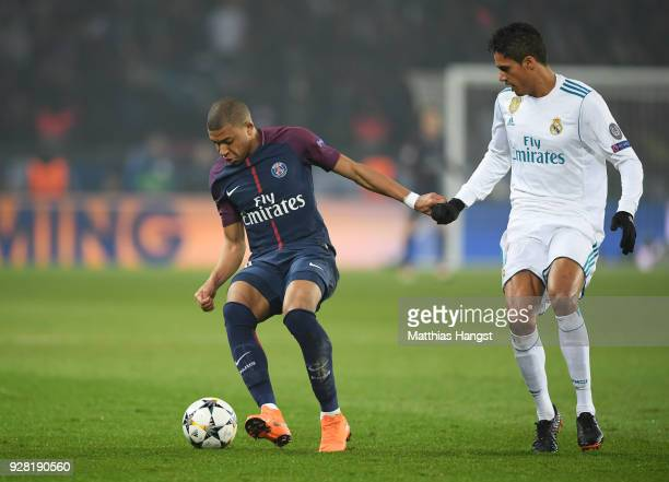 Kylian Mbappe of PSG is watched by Raphael Varane of Real Madrid during the UEFA Champions League Round of 16 Second Leg match between Paris...