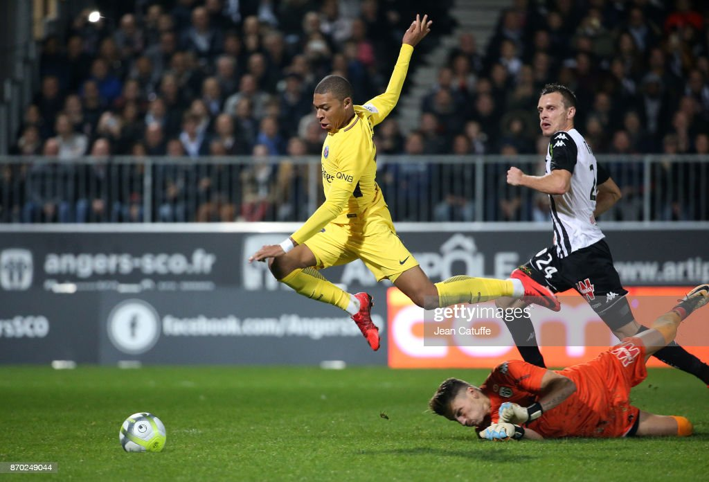 Kylian Mbappe of PSG passes by goalkeeper of Angers Mathieu Michel and Romain Thomas to score his second goal, the fifth for PSG during the French Ligue 1 match between Angers SCO and Paris Saint Germain (PSG) at Stade Raymond Kopa on November 4, 2017 in Angers, France.