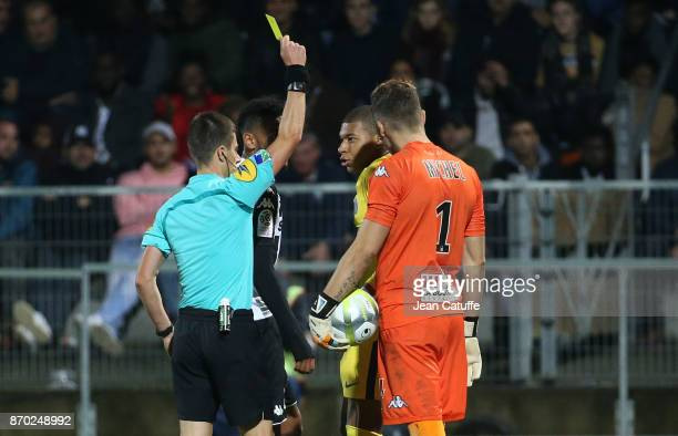 Kylian Mbappe of PSG receives a yellow card from referee Benoit Bastien during the French Ligue 1 match between Angers SCO and Paris Saint Germain at...