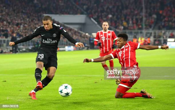 Kylian Mbappe of PSG shoots as David Alaba of Bayern Muenchen attempts to block during the UEFA Champions League group B match between Bayern...