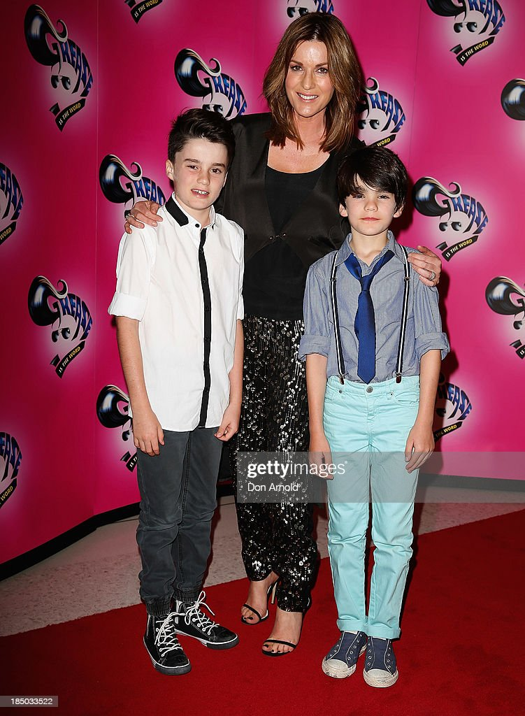 Kylie Gillies stands behind sons Gus and Archie at the Sydney Premiere of GREASE at The Star on October 17, 2013 in Sydney, Australia.