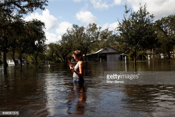Kylie Hughes films her surroundings as she waits in the flooded roadway of her campground for her mother to return from checking on their nearby...