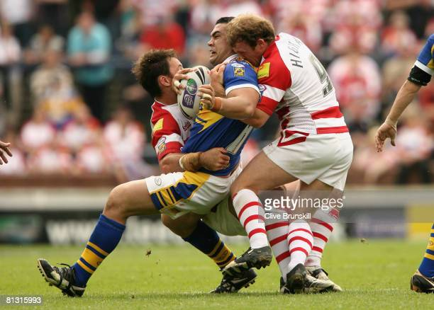 Kylie Leuluai of the Leeds Rhinos is tackled by Mickey Higham of the Wigan Warriors during the Carnegie Challenge Cup match between Leeds Rhinos and...