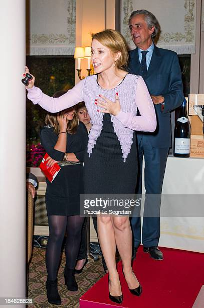 Kylie Minogue takes part to the wine auction as Christie's auctioneer Lionel Gosset looks on during the 'APREC' cancer research association benefit...