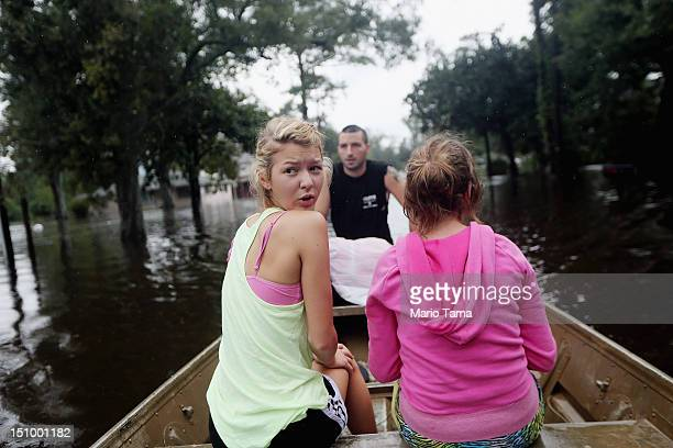 Kylie Trumbaturi and her sister Brittany depart their flooded home with family member Joshua Barbot who came to rescue family members in a boat on...