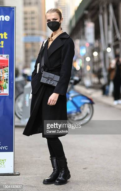 Kylie Vonnahme is seen wearing a black coat, tan shirt, black pants and boots with a Christian Dior bag outside the Christian Siriano show during New...