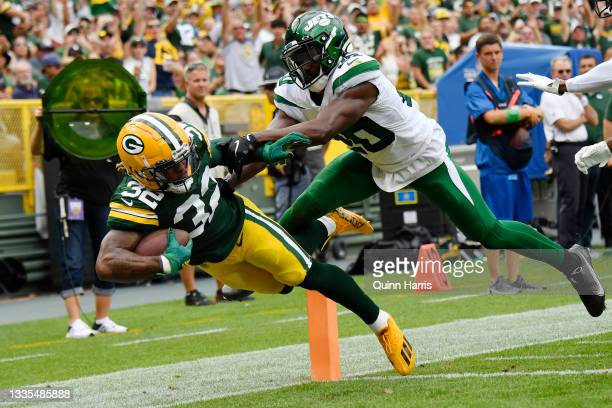 Kylin Hill of the Green Bay Packers scores a touchdown against Marcus Maye of the New York Jets in the first half during a preseason game at Lambeau...