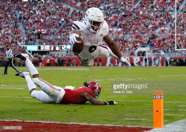 Kylin Hill of the Mississippi State Bulldogs dives for a touchdown over Shyheim Carter of the Alabama Crimson Tide at BryantDenny Stadium on November...
