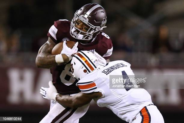 Kylin Hill of the Mississippi State Bulldogs runs with the ball as Noah Igbinoghene of the Auburn Tigers defends during the second half at Davis Wade...