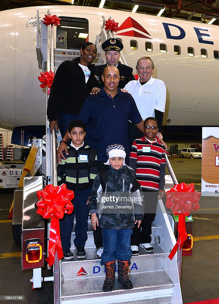 Kym Hampton, John Starks and Rod Gilbert pose with children and a Delta pilot at the 3rd Annual Garden of Dreams Foundation & Delta Air Lines' 'Holiday in the Hangar' event at John F. Kennedy International Airport on December 11, 2012 in New York City.