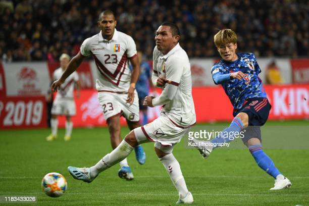 Kyogo Furuhashi of Japan shoots the ball under the pressure from Bernaldo Manzano of Venezuela during the international friendly match between Japan...
