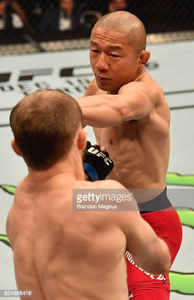 Kyoji Horiguchi of Japan punches Ali Bagautinov of Russia in their flyweight bout during the UFC Fight Night at the SSE Arena on November 19, 2016 in...