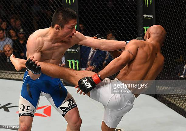 Kyoji Horiguchi of Japan punches Demetrious Johnson of the United States in their UFC flyweight championship bout during the UFC 186 event at the...