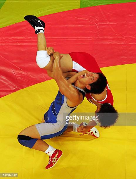 Kyoko Hamaguchi of Japan flips Xu Wang of China during the women's Freestyle wrestling 72 kg Semi Final round on August 23, 2004 during the Athens...