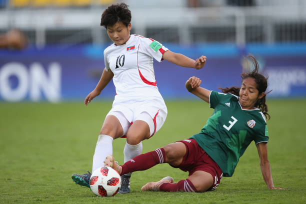 c7c02f894fe Kyong Yong Kim of Korea DPR is tackled by Miriam Garcia of Mexico during  the FIFA