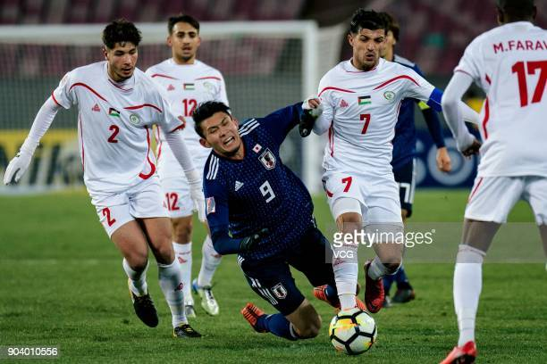 Kyosuke Tagawa of Japan and Mahmoud Abu Warda of Palestine compete for the ball during the AFC U23 Championship Group B match between Japan and...