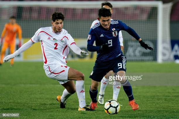 Kyosuke Tagawa of Japan and Michel Termanini of Palestine compete for the ball during the AFC U23 Championship Group B match between Japan and...
