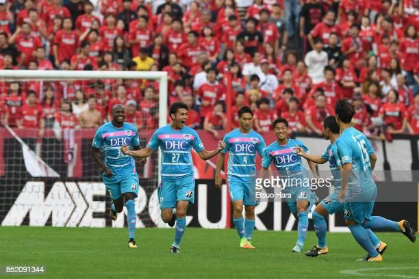 Kyosuke Tagawa of Sagan Tosu celebrates scoring his side's first goal with his team mates during the JLeague J1 match between Urawa Red Diamonds and...