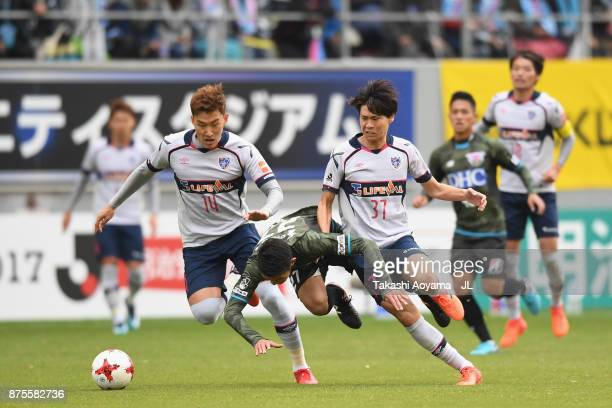 Kyosuke Tagawa of Sagan Tosu is challenged by Jang Hyun Soo and Kento Hashimoto of FC Tokyo during the JLeague J1 match between Sagan Tosu and FC...