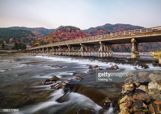 kyoto, japan. famous bridge across river hozugawa in arashiyama - arashiyama stock pictures, royalty-free photos & images