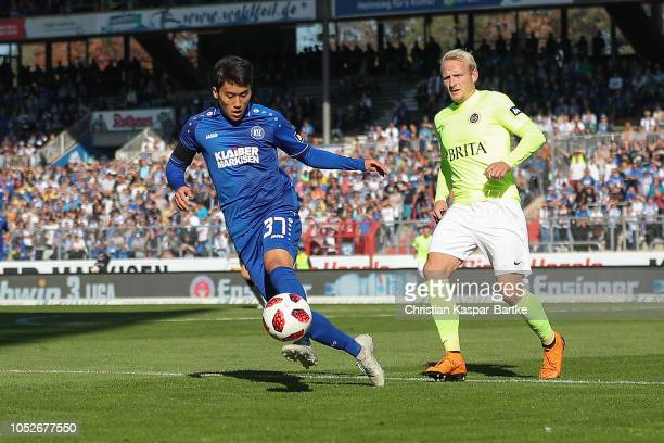 KyoungRok Choi of Karlsruher SC challenges Alf Mintzel of SV Wehen Wiesbaden during the 3 Liga match between Karlsruher SC and SV Wehen Wiesbaden at...
