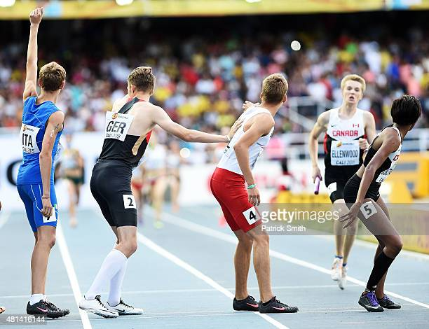 Kyra Constantine prepares to take the baton from Dean Ellenwood of Canada during the Mixed 4 x 400 Meters Relay against on day five of the IAAF World...