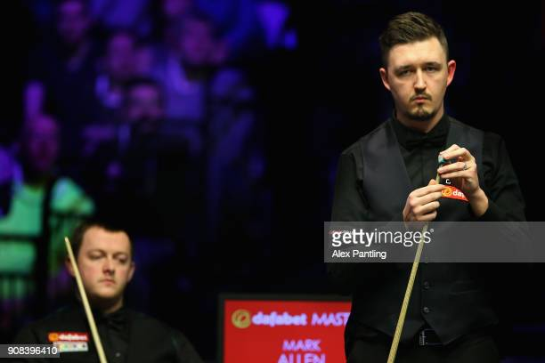 Kyren Wilson chalks his que as Mark Allen watches on during The Dafabet Master Final between Kyren Wilson and Mark Allen at Alexandra Palace on...