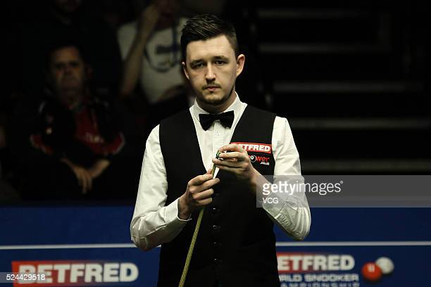 Kyren Wilson of England chalks his cue in the quarterfinals against Mark Selby of England on day eleven of Betfred World Championship 2016 at The...