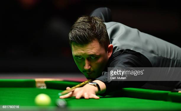 Kyren Wilson of England plays a shot during his first round match against Ding Junhui of China on day one of the Dafabet Masters at Alexandra Palace...
