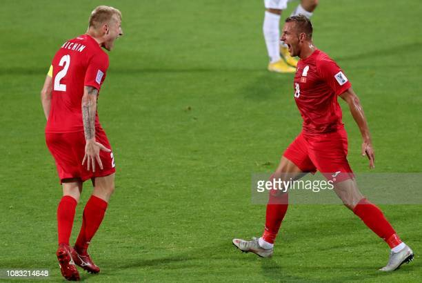 Kyrghyzstan's forward Vitalij Lux reacts with Kyrghyzstan's defender Valerii Kichin after the former scored a goal during the 2019 AFC Asian Cup...
