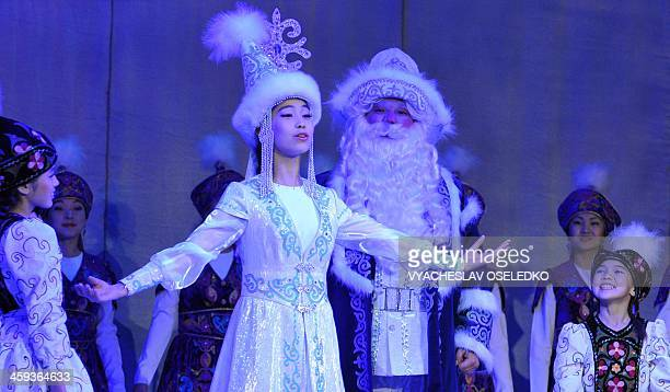 Kyrgyz actors dressed as Ded Moroz Russian Santa Claus and Snegurochka his companion take part a performance to mark the upcoming New Year's holiday...