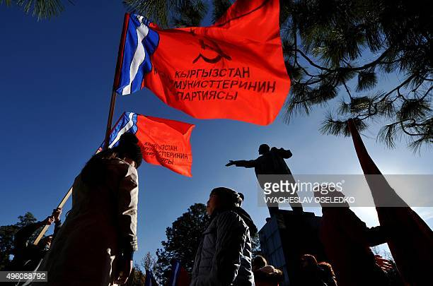 Kyrgyz communist party supporters hold red flags in front of monument to the Soviet Union founder Vladimir Lenin during a rally to mark the 98th...