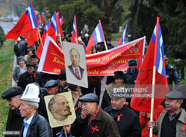 Kyrgyz communist party supporters hold their red flags and portraits of the Soviet Union founder Vladimir Lenin during a rally to mark the 97th...