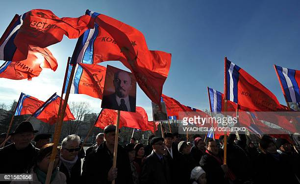 TOPSHOT Kyrgyz communist party supporters holding red flags gather in front of a monument to the first Soviet leader Vladimir Lenin during a rally to...