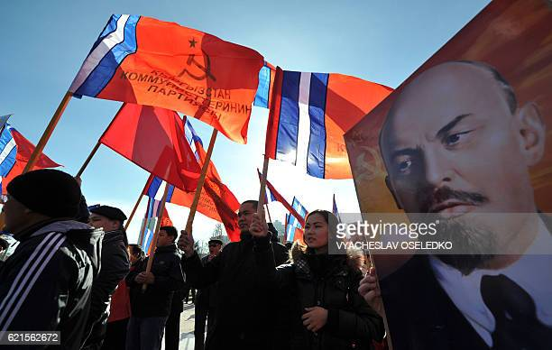 Kyrgyz communist party supporters holding red flags gather in front of a monument to the first Soviet leader Vladimir Lenin during a rally to mark...