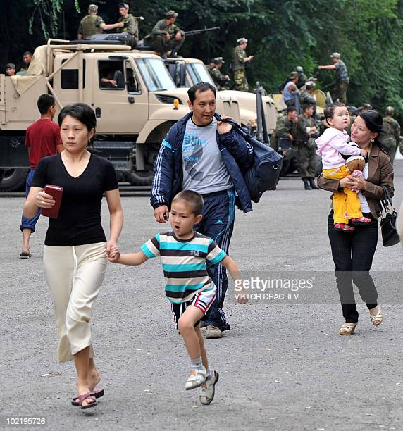Kyrgyz families walk to the board the bus leaving to Bishkek in central Osh on June 17, 2010. Deadly inter-ethnic clashes that erupted in Kyrgyzstan...