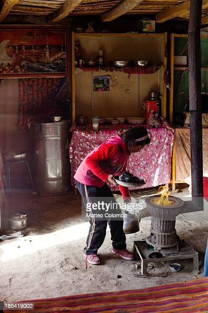 Kyrgyz girl putting coal in the stove in her yurt