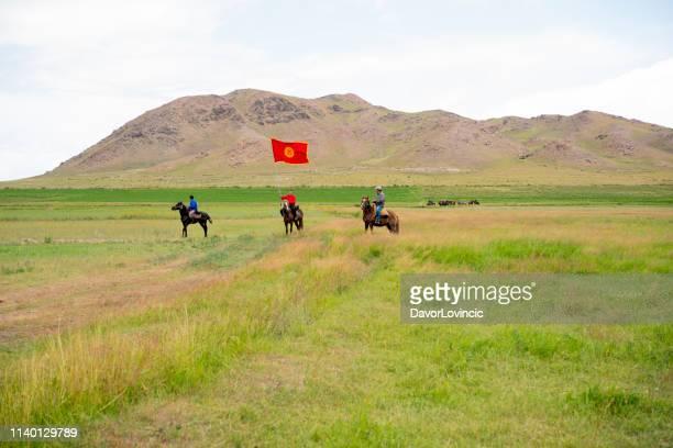 キルギスの鳥や獲物の祭りでは、草原の旗と騎手 - キルギス ストックフォトと画像