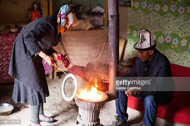 Kyrgyz man and woman near the stove inside a yurt