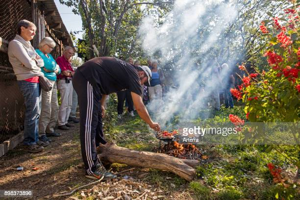 Kyrgyz man cooking food for tourists on a traditional stone barbecue in Kyrgyzstan