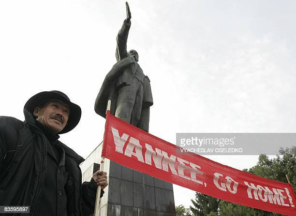 A Kyrgyz man holds a banner during a rally marking the 91st anniversary of the October revolution near a monument to Soviet leader Vladimir Lenin the...
