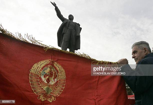 A Kyrgyz man holds a red Communist flag during a rally marking the 91st anniversary of the October revolution near a monument to Soviet leader...