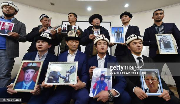 Kyrgyz men hold portraits of their relatives as they attend a press conference in Bishkek on November 29 2018 Citizens of exSoviet Kyrgyzstan who...