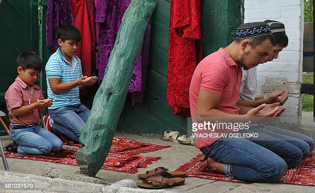 Kyrgyz muslims pray on the first day of Eid alFitr at a mosque in Karakol 400km from Bishkek on July 17 2015 Muslims around the world celebrate Eid...