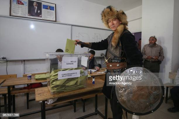 Kyrgyz origin Turkish citizen casts his vote at a polling station during the parliamentary and presidential elections in Ercis district of Van Turkey...