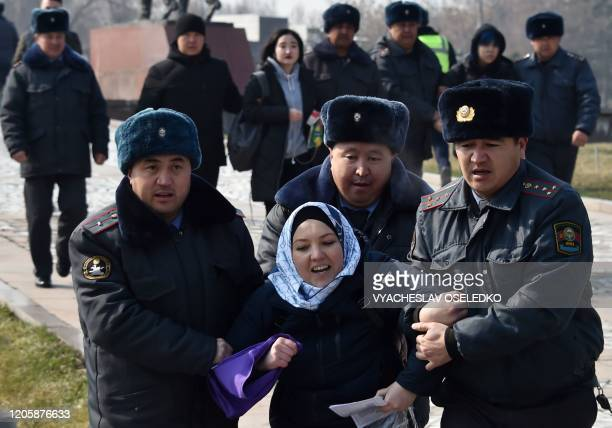 Kyrgyz police arrest a woman protesting against gender-based violence to mark International Women's Day in Bishkek on March 8, 2020. - The detentions...