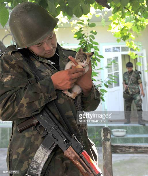 Kyrgyz police officer holds a kitten during the search of an ethnic Uzbek house in Osh on June 23, 2010. Authorities in Kyrgyzstan said on June 23...