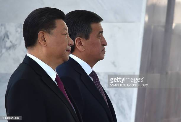 Kyrgyz President Sooronbay Jeenbekov and his Chinese counterpart Xi Jinping attend a welcoming ceremony prior to their talks in Bishkek on June 13,...
